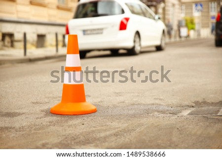 Repair work sign restricting traffic. White-orange plastic striped cone warning of danger. Tightening in traffic. Street of the old city with cars. Roadway repair. Poor asphalt on the road. Attention  #1489538666