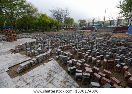 Repair work. Street pavers piled up in piles in a park in open air.