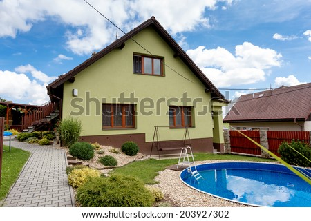 repaired rural house, fixed facade, insulation and painted to green  color witg swimming pool