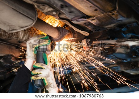 repairing of corrugation muffler of exhaust system in car workshop - repairer cuts old silencer on car by angle grinder