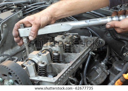 Repairing of modern diesel engine, workers hands and tool