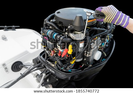 Repairing  outboard marine engine. Motorboat engine seasonal service and maintenance. Mechanic hand performing maintenance on outboard engine