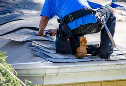 repairing the roof of a home; A worker replaces shingles on the roof of a home