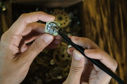 Repairing vintage watches. Girl craftsman dismantles clock.  Beautiful female fingers with pincers forceps at work. Female hands holding tweezers. Disassembly of clock on wooden table in soft focus.