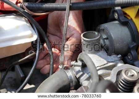 Repairing water pump of modern  engine, workers hands and tool