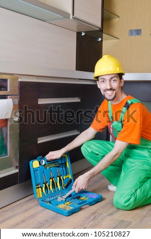 Repairman assembling the furniture at kitchen - stock photo