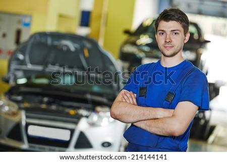 repairman auto mechanic portrait in car auto repair or maintenance shop service station