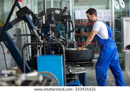 repairman balancing  car wheel on balancer in workshop Stock fotó ©