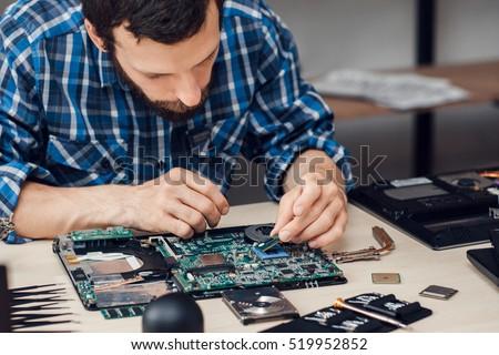repairman disassembling laptop...