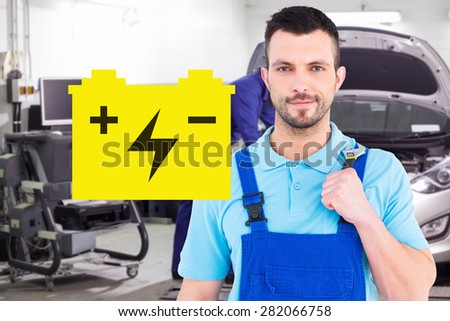 Repairman holding adjustable wrench against mechanic leaning on a car looking at the engine