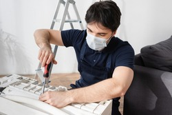 repairman in medical mask holding screwdriver and fixing broken air conditioner