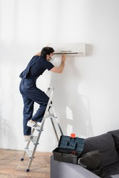 repairman in medical mask standing on ladder and fixing air conditioner in living room