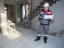 Repairman inside a house under construction. Repairman in uniform with blueprints in his hands. Man in a construction worker uniform. Career as apartment renovator. He examines a sheet of paper