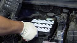Repairman installs a new air filter in a car engine