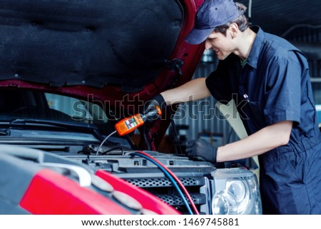 Repairman is conducting diagnostics and detecting problems of car conditioner by special freon leak tester at workshop auto repair shop. Mechahnic is repairing vehicle at service station garage.