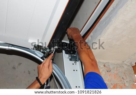 Repairman repair garage door opener. Garage door replacement, garage door repair.  #1091821826