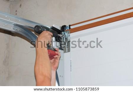 Repairman repair garage door opener. Garage door replacement, garage door repair.  #1105873859