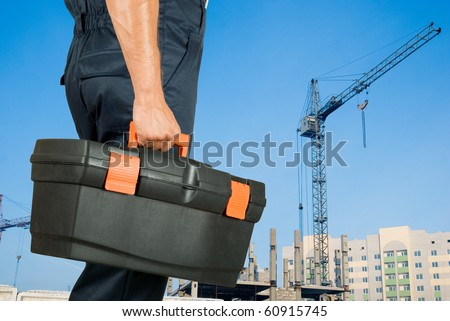 repairman with box of instruments on building background