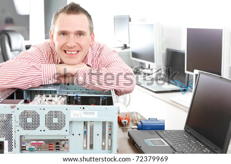 Repairman with computer, an owner of small business. Monitors and other laptops in the background waiting for service.