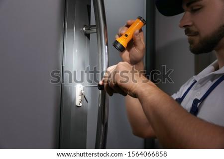 Repairman with flashlight fixing door lock, closeup