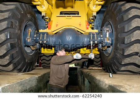 repairman worker screwing nuts of axle assembly in heavy wheel loader