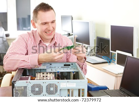 Repairman working with computer with a part in hands. Monitors and other laptops in the background waiting for service.
