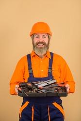 Repairment tools. Worker holds repair tools. Building. Industry. Technology. Spanner. Bearded builder. Builder in construction helmet. Hard hat. Industrial worker. Repair. Hammer. Screwdriver.