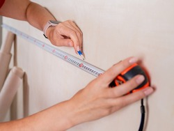 Repairs in the apartment. Close-up of a tape measure and pencil in women's hands. Measuring the walls in a room.