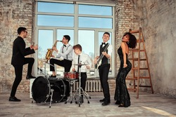 Repetition of multi ethnic jazz band in loft. Bass guitar player, electric guitar player, saxophonist and drummer at loft. Jazz music and jam session concept. passion for music and youth culture