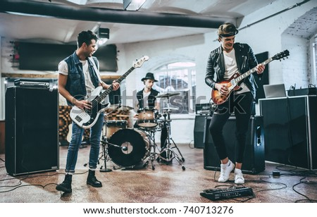 Repetition of rock music band. Bass guitar player, electric guitar player and drummer behind the drum set. Rehearsal base #740713276