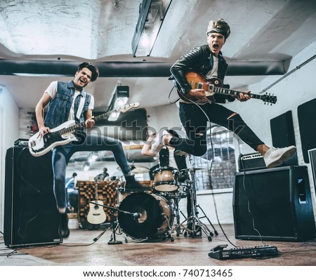 Repetition of rock music band. Bass guitar player, electric guitar player and drummer behind the drum set. Rehearsal base #740713465