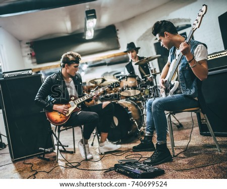 Repetition of rock music band. Bass guitar player, electro guitar player and drummer behind the drum set. Rehearsal base #740699524