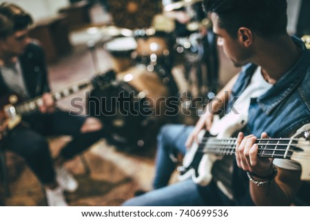 Repetition of rock music band. Bass guitar player, electro guitar player and drummer behind the drum set. Rehearsal base Foto stock ©