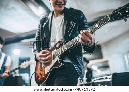 Stock Photo Repetition of rock music band. Cropped image of electric guitar player and drummer behind the drum set. Rehearsal base