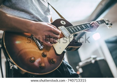Repetition of rock music band. Cropped image of electric guitar player. Rehearsal base