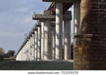 Repetitive pillars below bridge into the distance #753319270