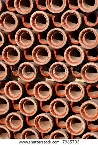 Repetitive stack of clay pipes on construction site