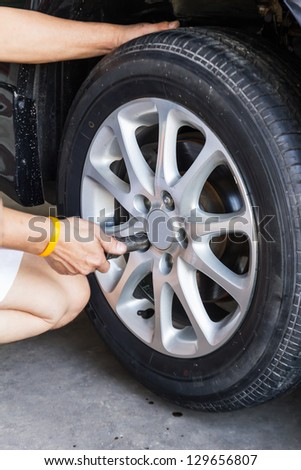 Replacing lug nuts by hand while changing tires on a vehicle.