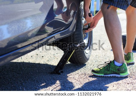 Replacing the car wheel. Photo of the car wheel repair process. Accident on the road. Punctured car wheel. The man takes off the wheel of a car #1132021976