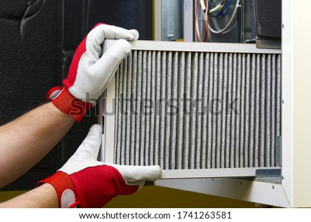 Photo of  Replacing the filter in the central ventilation system. Replacing Dirty Air filter for home central air conditioning system. Change filter in rotary heat exchanger recuperator.