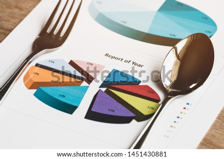 Report of year. fork spoon on document charts graphs show report results for successful of work business and analyzing financial diagram statistics reports or marketing research planning.