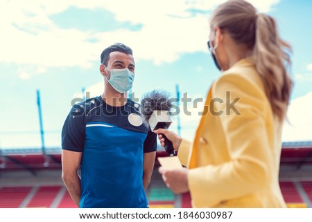 Reporter doing interview with football player during covid-19 wearing masks in soccer stadium Foto stock ©