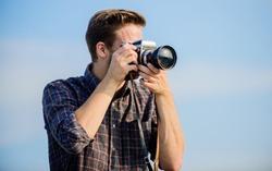 Reporter taking photo. Manual settings. Travel blogger. Vintage equipment. Hipster photographer. Blogger shooting vlog. Guy outdoors blue sky background. Handsome blogger guy traveler retro camera.