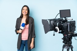 Reporter woman holding a microphone and reporting news isolated on blue background laughing