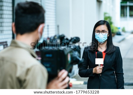 Reporter woman holding a microphone with reporting news and cameraman shooting outdoor news update while wearing  mask prevent Covid-19 or coronavirus quarantine pandemic.