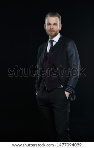 Representative man with a beard in a three-piece suit isolated on a black background.