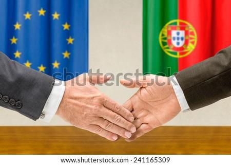 Representatives of the EU and Portugal shake hands