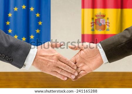 Representatives of the EU and Spain shake hands
