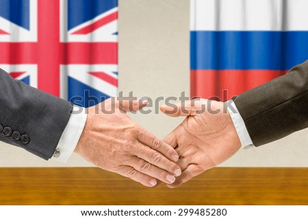 Representatives of the UK and Russia shake hands