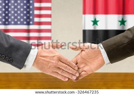 Representatives of the USA and Syria shake hands